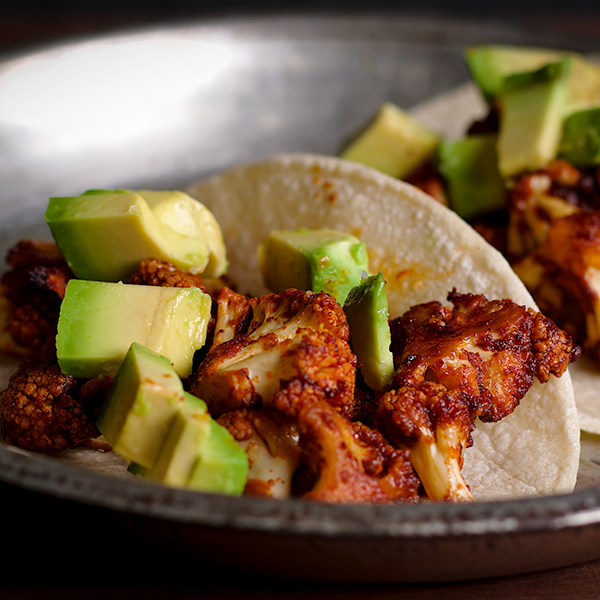 A vegan cauliflower taco with avocado slices.