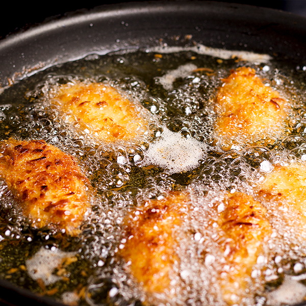 Frying pieces of crispy coconut lime chicken in hot oil.