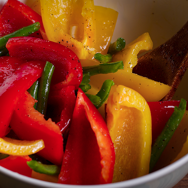Tossing sliced bell peppers and green beans in a bowl with olive oil and seasoning before using them to make The Ultimate Sheet Pan Dinner.