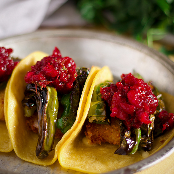Three shishito pepper tacos with fried cheese and chili cranberry sauce on a plate.