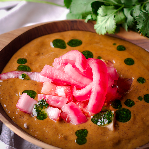 A bowl of black bean soup topped with pickled onions and cilantro oil.