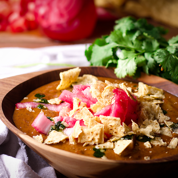 A bowl of black bean soup topped with cilantro oil, chopped fresh tomatoes, pickled onions, and crushed tortilla chips,