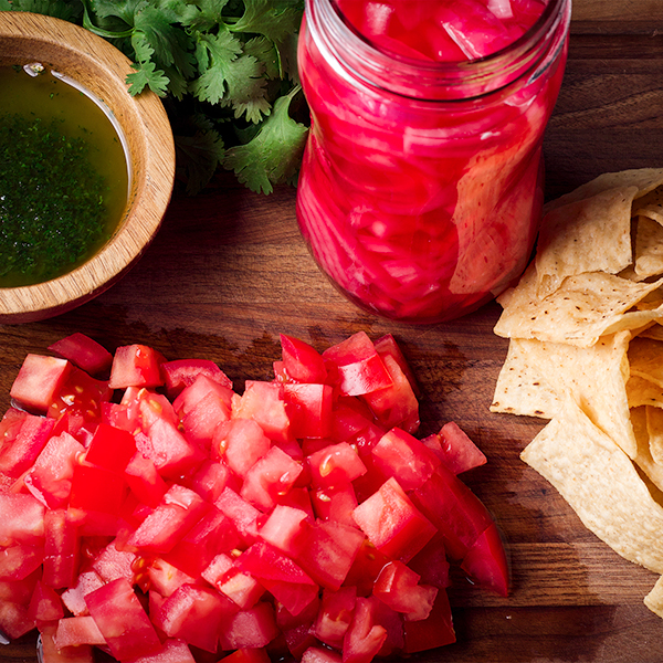 A tray of toppings for black bean soup: chopped tomatoes, cilantro oil, pickled onions, and tortilla chips.