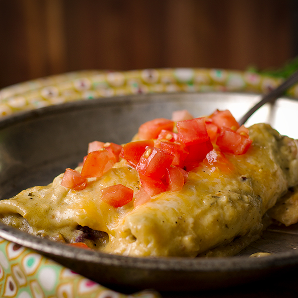 Black Bean Enchiladas with Creamy Tomatillo Sauce and chopped tomatoes on a plate ready to eat.