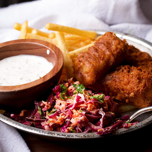 A plate of fish and chips with homemade tartar sauce and cabbage slaw.