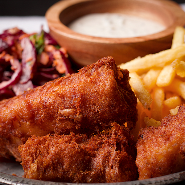 A plate of light and crispy beer battered fried fish with French fries, coleslaw and tartar sauce.