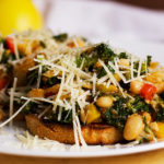 A plate with two slices of toast topped with white beans, veggies and greens, sprinkled with grated parmesan cheese.