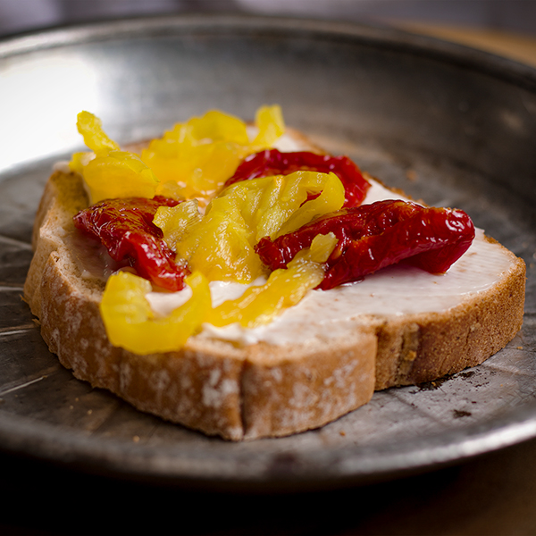 A piece of toast with mayonnaise, banana peppers, and sun dried tomatoes.