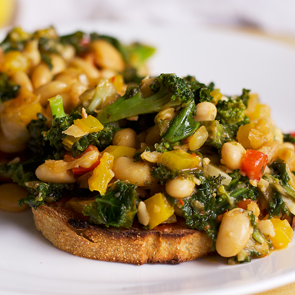 A plate with two slices of toast topped with white beans, veggies and greens.
