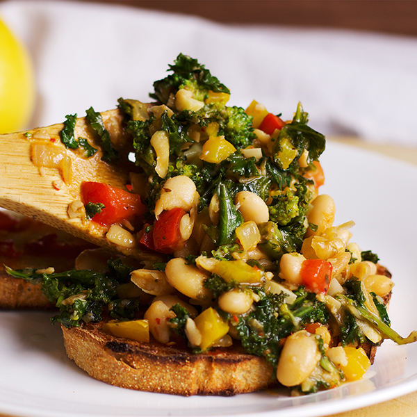 Spooning white beans, veggies, and greens over toast.