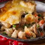 A piece of classic double crust chicken pot pie on a plate with a fork.
