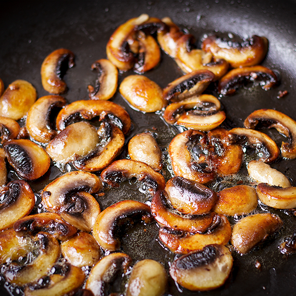 Sliced mushrooms cooking in a skillet with butter.