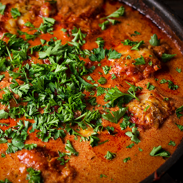 A pan of Chicken Paprikash sprinkled with chopped, fresh parsley.
