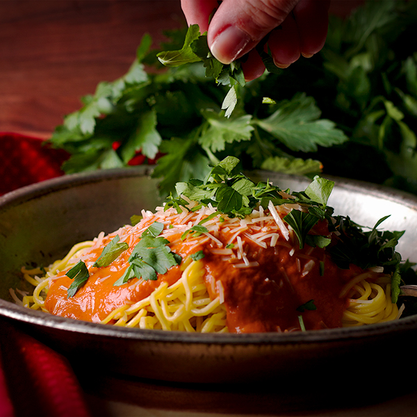 Sprinkling chopped fresh parsley over a plate of pasta with creamy red pepper sauce.