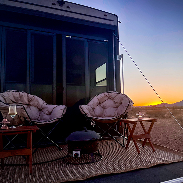 The back deck of our RV while we are parked in Ironwood Forest National Monument in Arizona, with a sunset in the background.