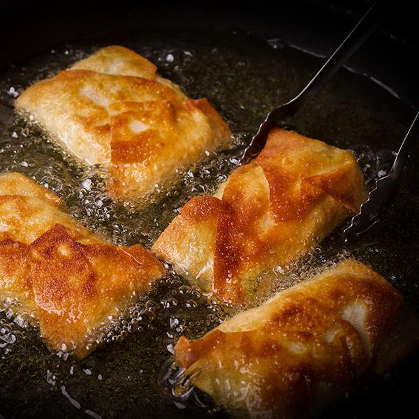 Frying crispy chili rellenos in hot oil.