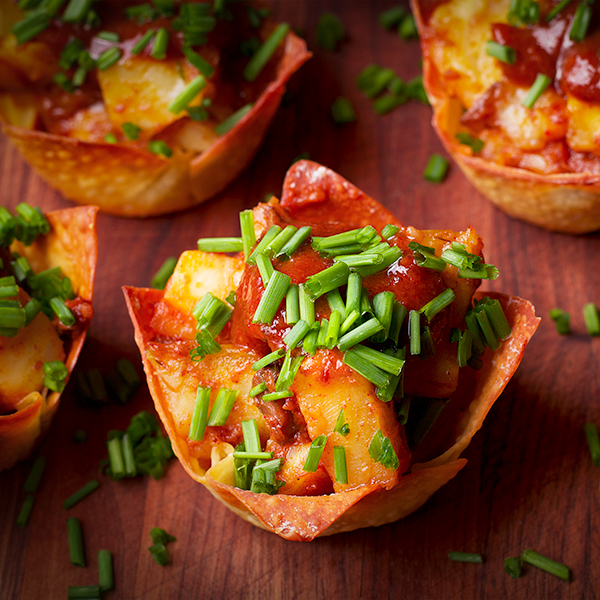 A tray of Roasted Celery Root, Mushroom, and Goat Cheese Wonton Cups with Date BBQ Sauce and Chili Oil.