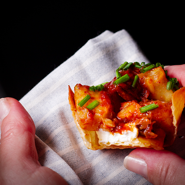 Someone holding a Roasted Celery Root, Mushroom, and Goat Cheese Wonton Cup with Date BBQ Sauce and Chili Oil on a cloth napkin.