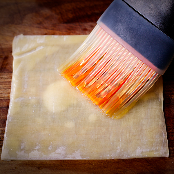 Brushing a wonton wrapper with olive oil.