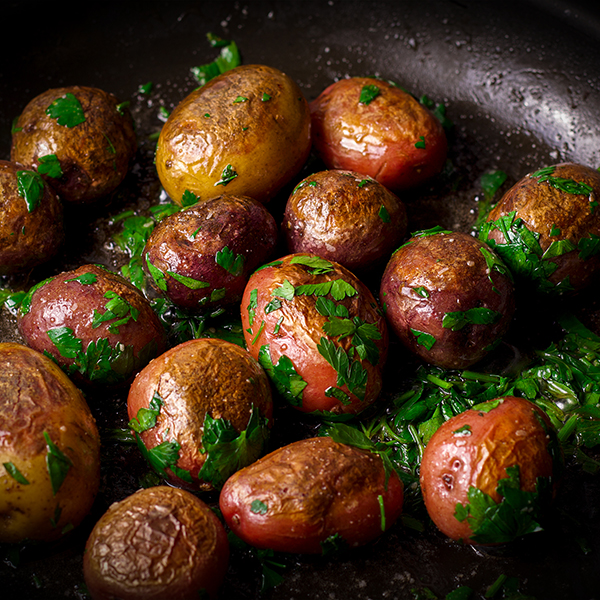 A pan of whole small potatoes cooked in butter with fresh parsley.
