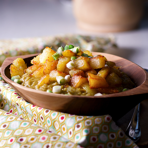 A bowl of split pea soup with ham, topped with crispy fried potatoes and sliced green onions.