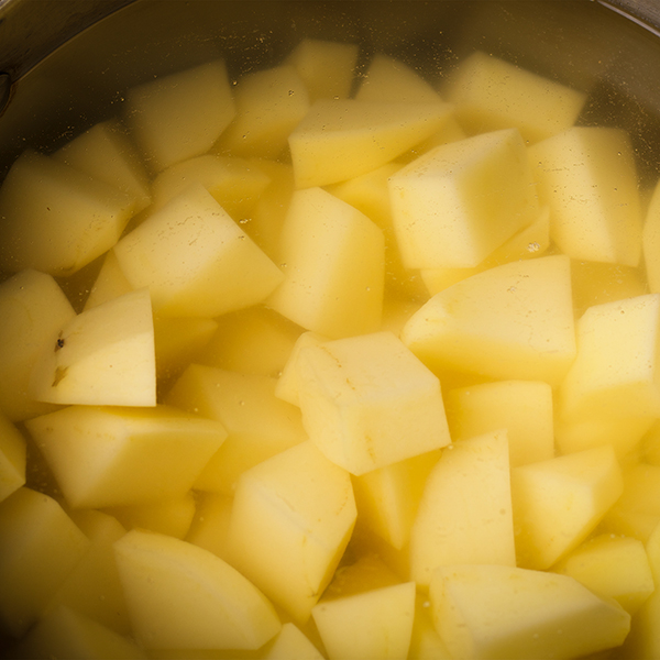 Cubes of Yukon Gold potatoes in a pot of salted water.
