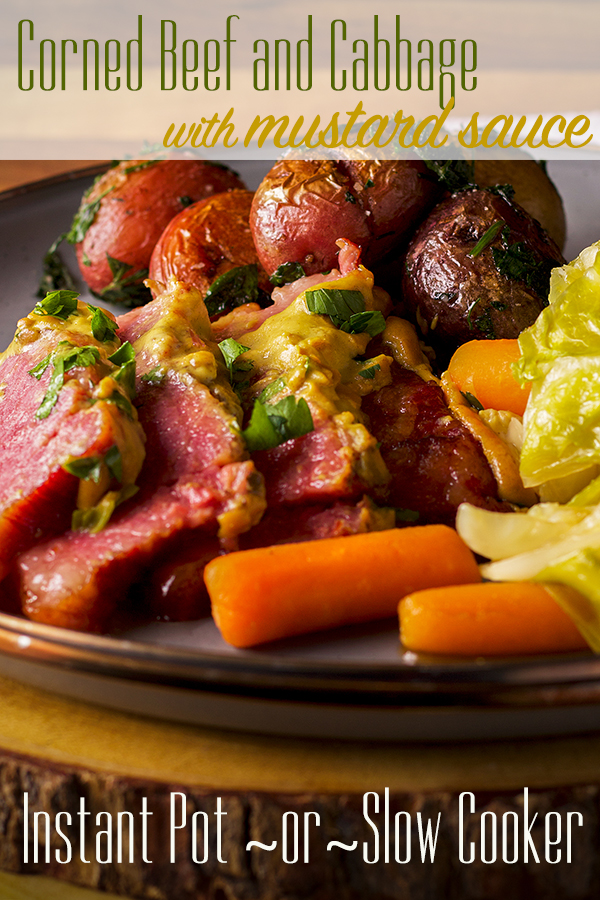 A plate filled with corned beef and cabbage with mustard sauce, carrots, and parsley buttered potatoes.