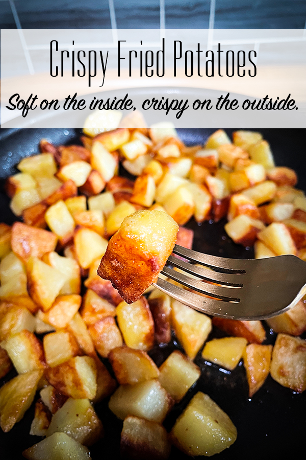 A fork with one crispy fried potato on it and a pan of crispy fried potatoes in the background.