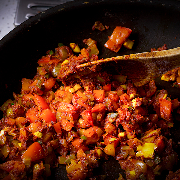 Stirring the spices and vegetables in a skillet to make red lentil dal.