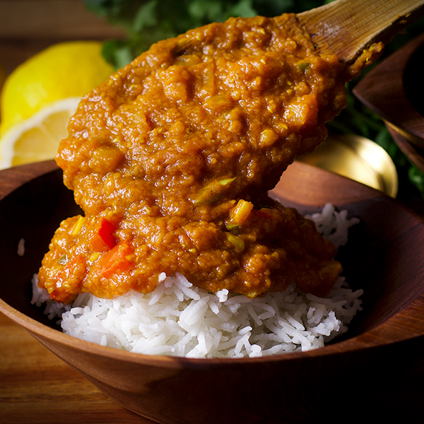 Spooning red lentil dal into a bowl of white rice.