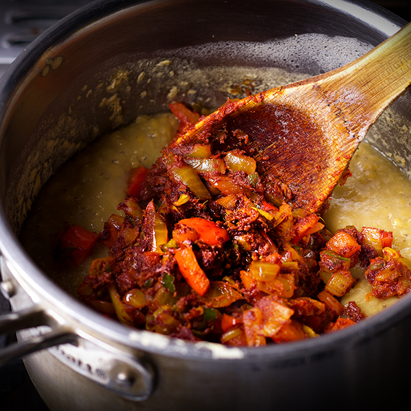 Stirring spices and vegetables into a pot of red lentils to make lentil dal.