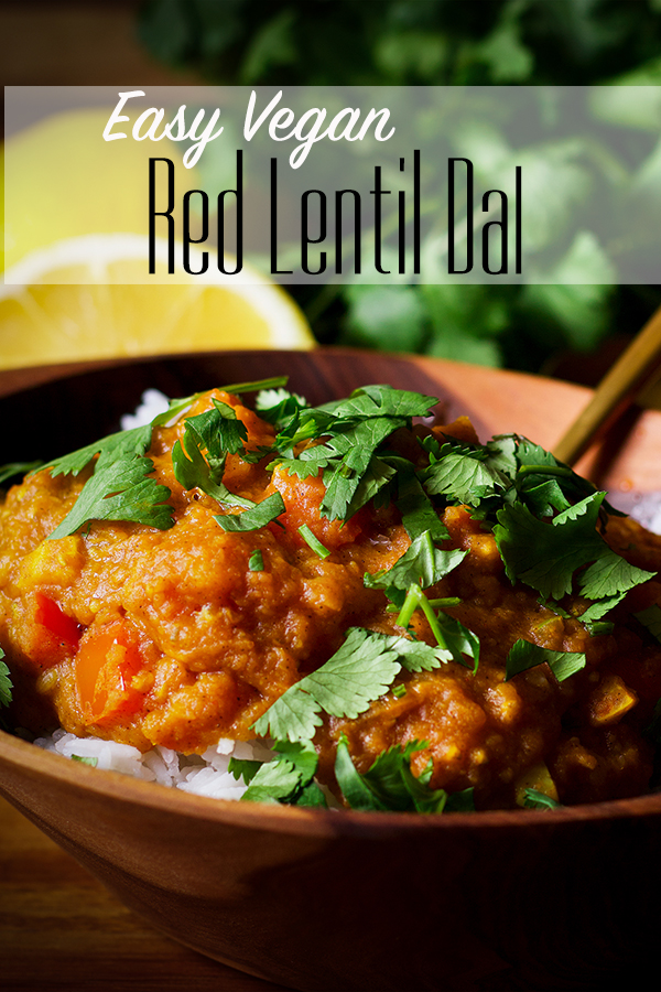 A wood bowl filled with rice and homemade red lentil dal.