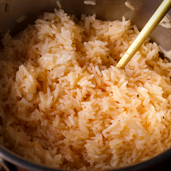 Using a fork to toss cooked white rice with sriracha vinaigrette.