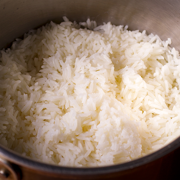 A saucepan filled with cooked white rice.