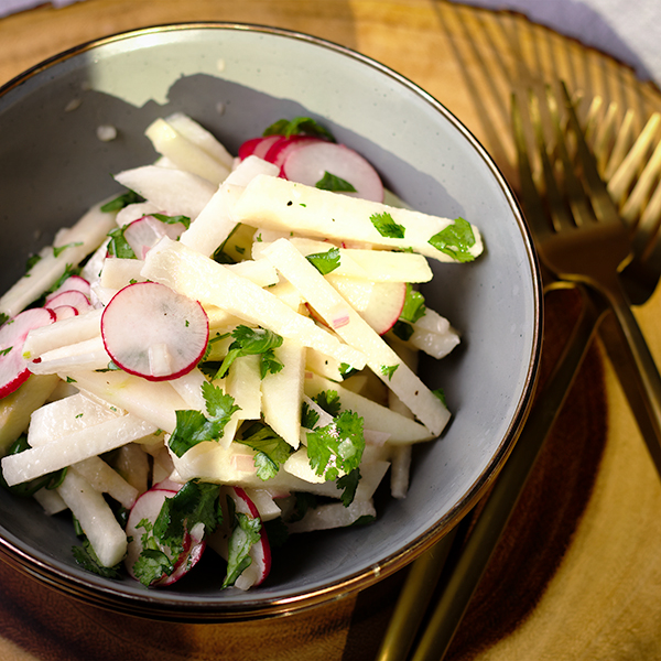 A bowl filled with jicama salad with honey lime dressing.