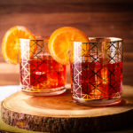 Two glasses on a wood serving board filled with ice and pomegranate margaritas and garnished with orange slices.