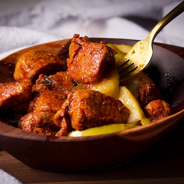 A gold fork lifting a Spanish Pork Bite and Fried Apple from a wood bowl.