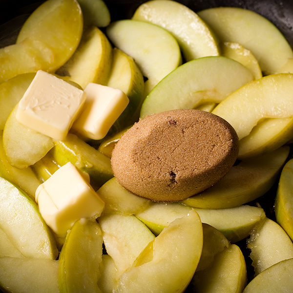 Adding brown sugar and butter to sliced green apples in a pan.