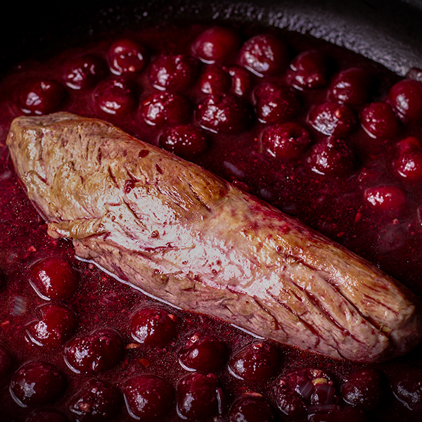 A pork tenderloin in a skillet with red wine cherry sauce.