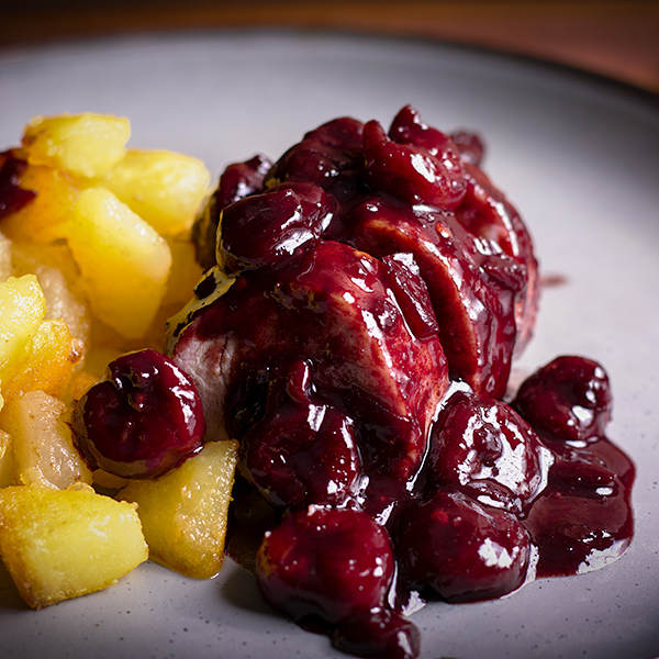A plate with slices of roasted pork tenderloin with red wine cherry sauce and crispy potatoes.
