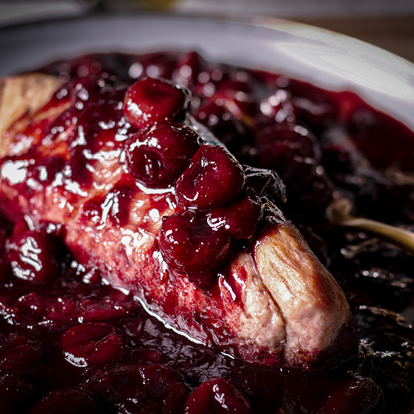 Roasted pork tenderloin on a plate covered in red wine cherry sauce.