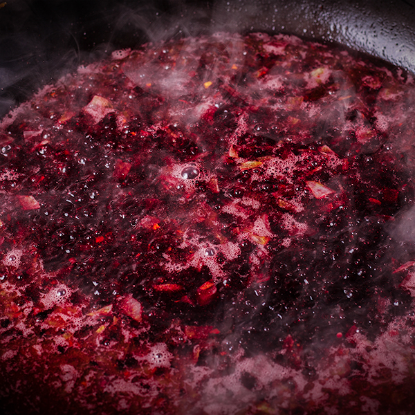 Red wine cherry sauce simmering in a skillet.