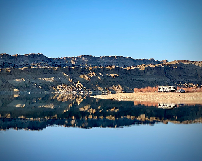 Our 5th wheel RV parked on a beach right next to the water at The Flaming Gorge in Utah.