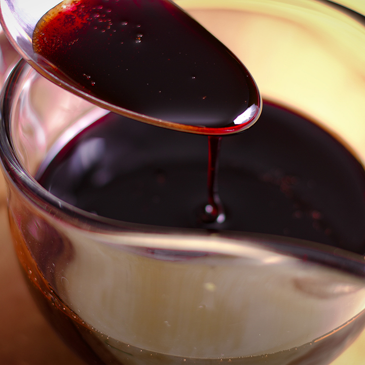 A small glass pitcher of pomegranate molasses.