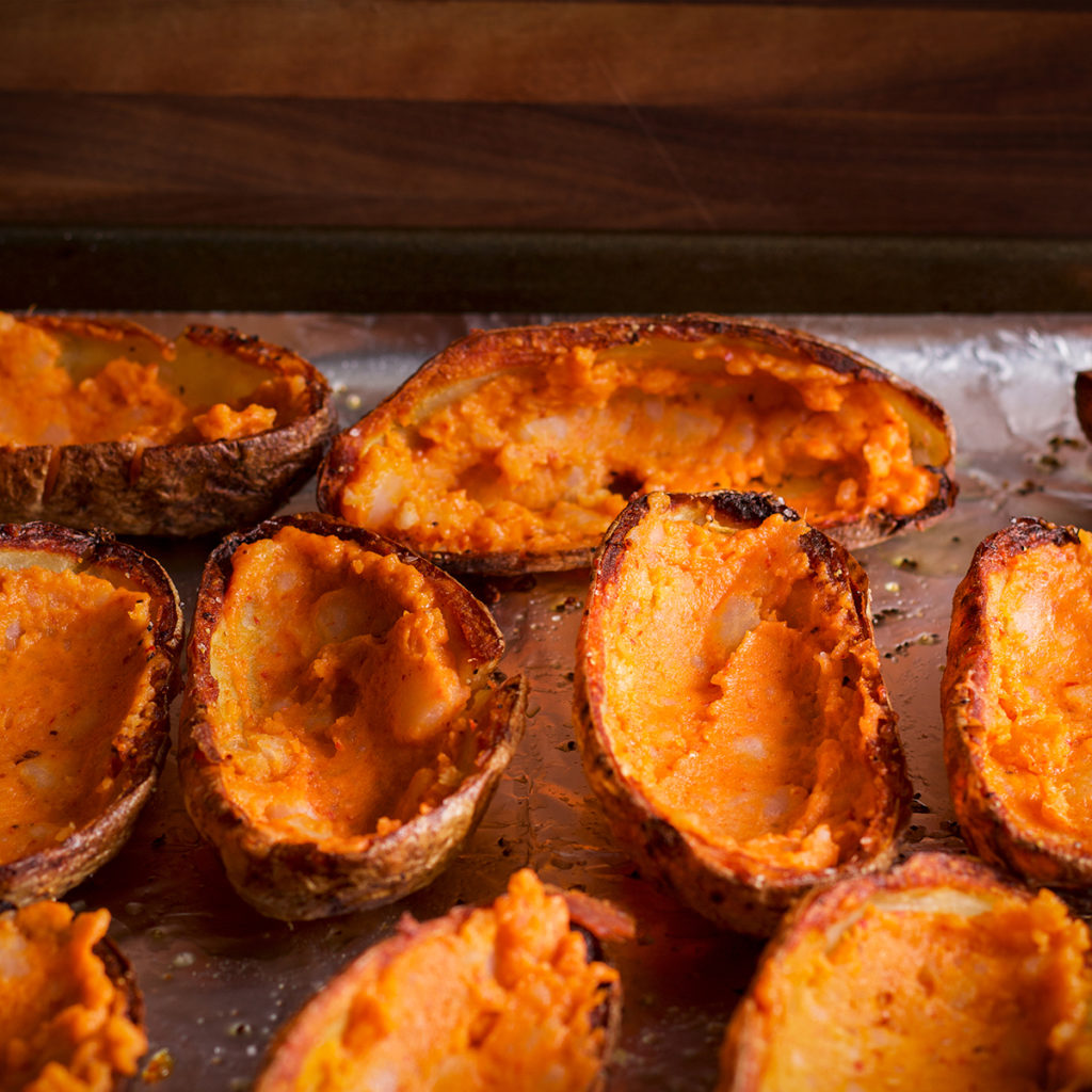 A tray of baked potato skins that have been filled with kimchi mayo mashed potato.