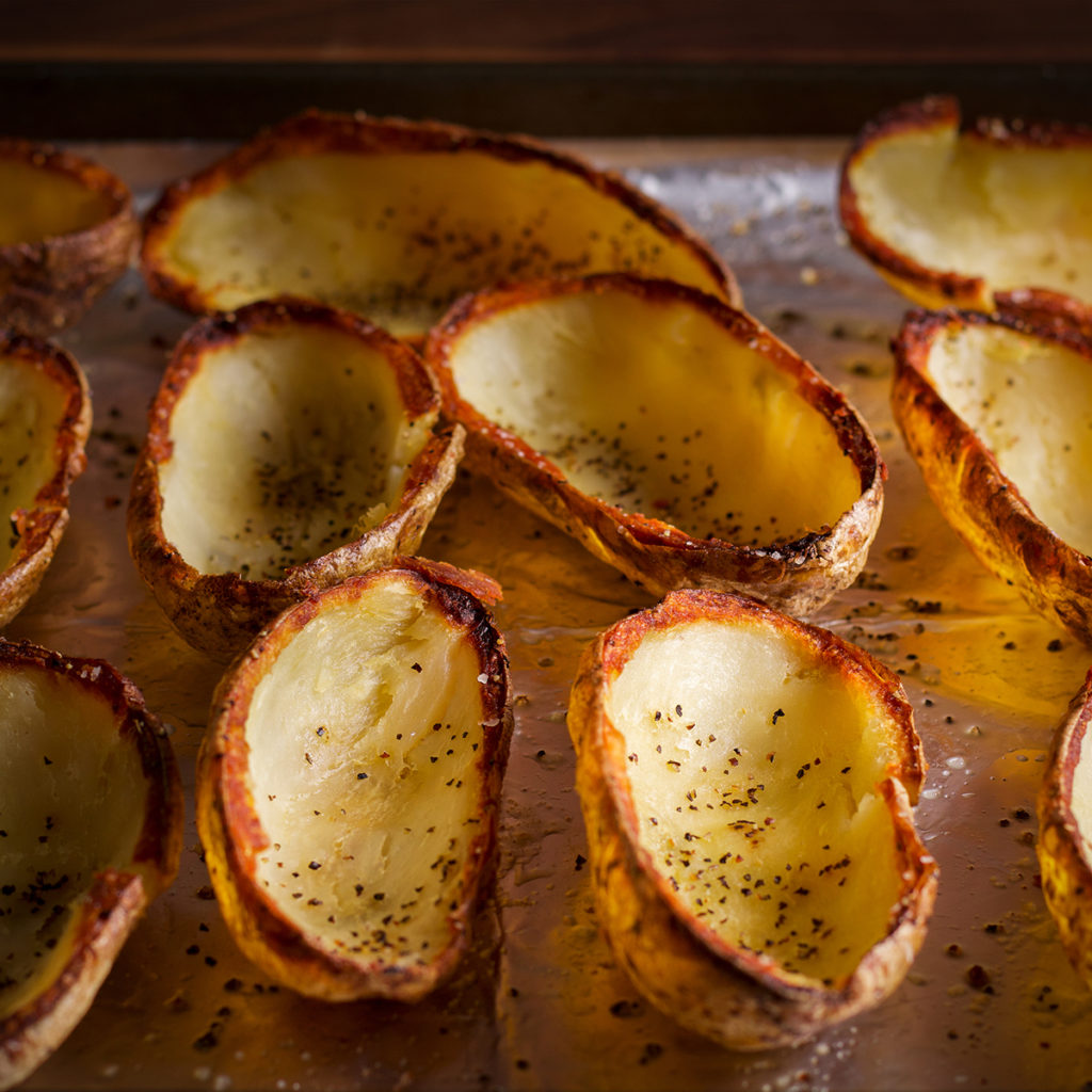 A baking sheet with crispy potato skins ready to be filled.
