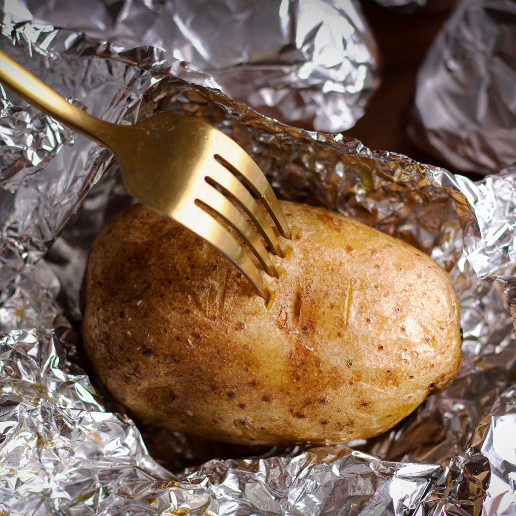Poking a baked potato with a fork to see if it's done cooking.