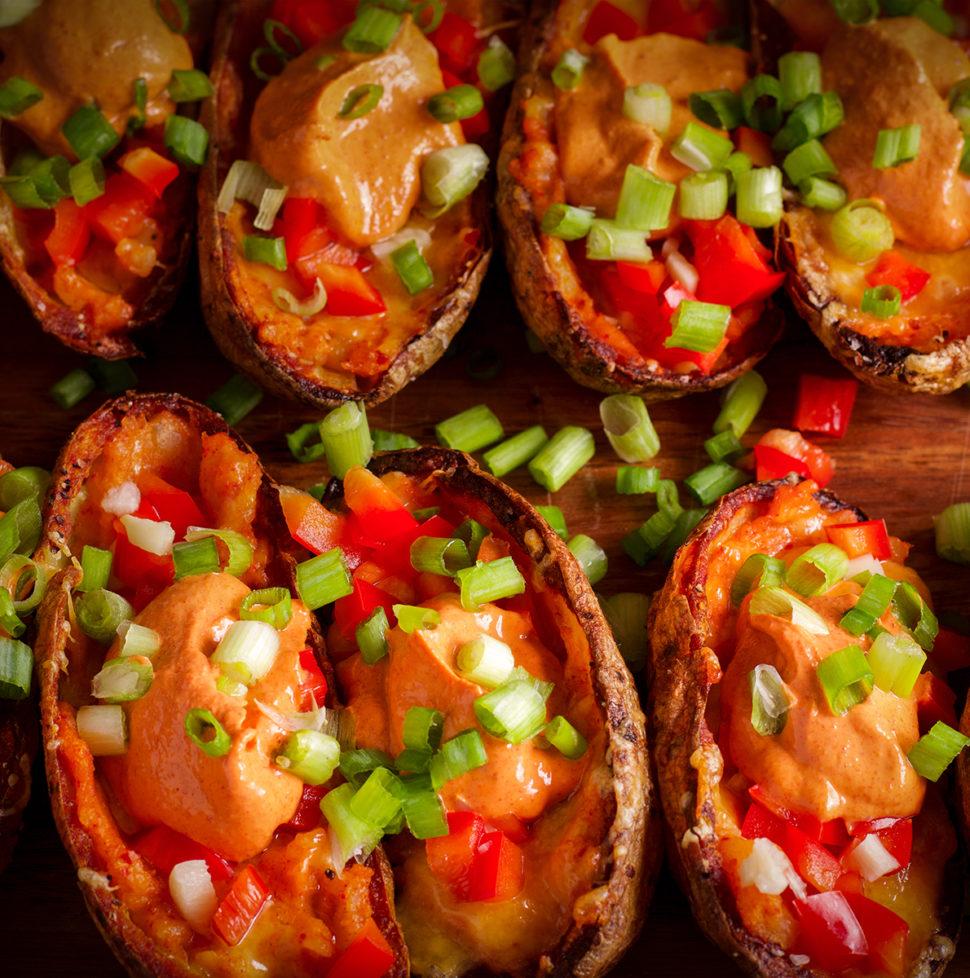 A wood tray of baked potato skins with kimchi mayo and Gochujang sauce.