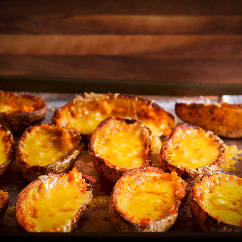 A tray of baked potato skins filled with melted cheddar cheese.