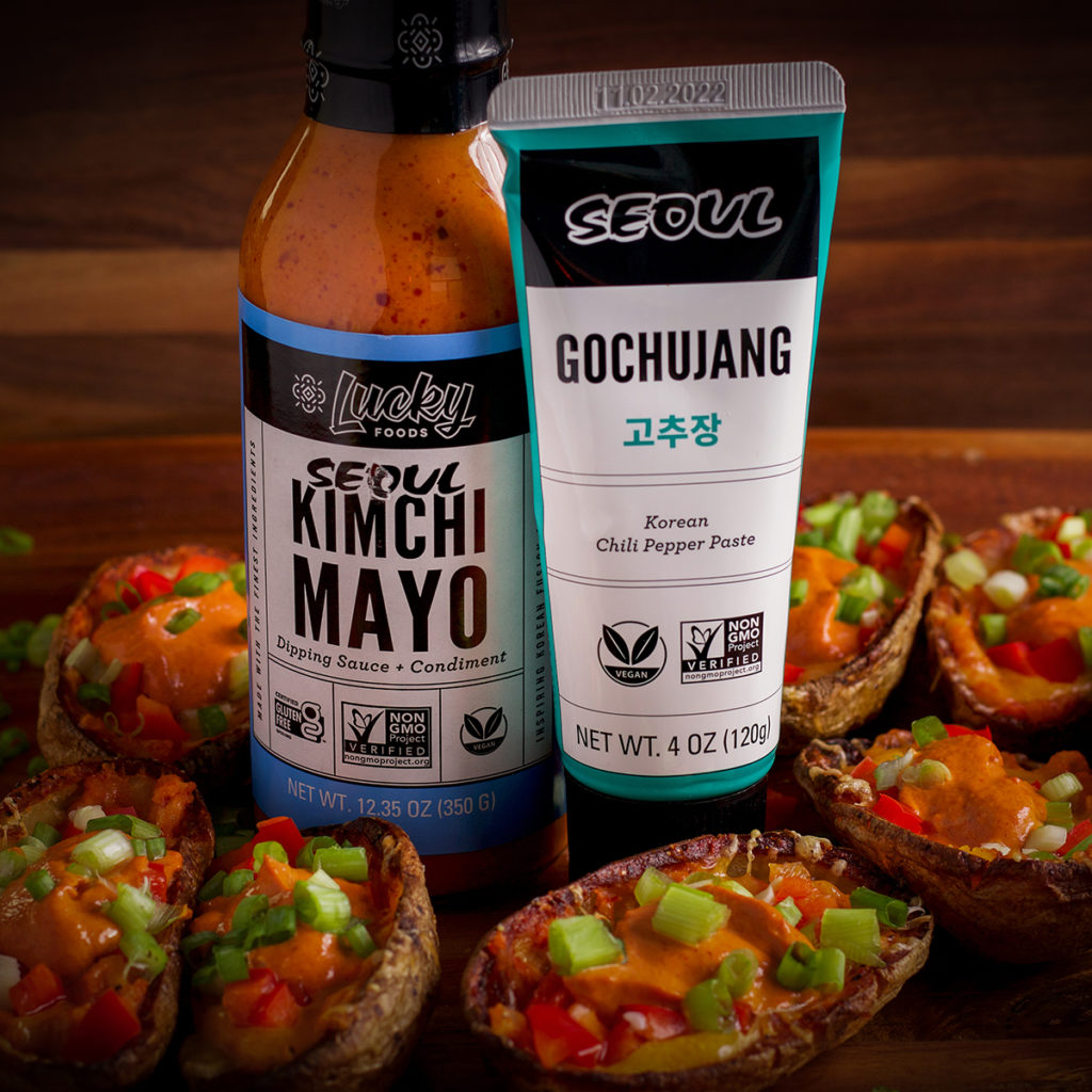 A bottle of Kimchi Mayo and a tube of Gochujang sauce on a tray with baked potato skins.